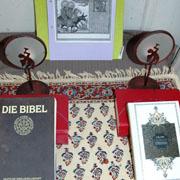 Karikatur mit Jesus und Mohammed vor Bibel und Koran.