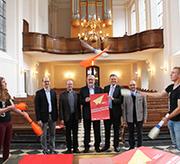 Präsentation der Pläne zum Ökumenischen Kirchentag Aachen 2017, v.l. Salvatore di Noia, Msgr. Gregor Huben, Superintendent Hans-Peter Bruckhoff, Redmer Studemund und Armin Drack, eingerahmt von zwei Mitgliedern des Zirkus Configurani.