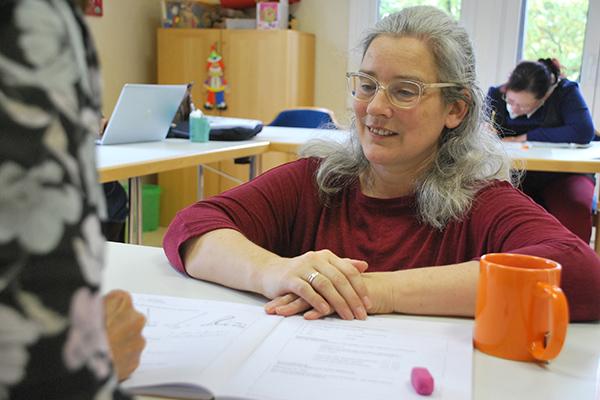 """Alexandra Wust unterstützt die Besucher des Kurses """"Lesen und Schreiben – für Erwachsene"""" im Evangelischen Erwachsenenbildungswerk in Simmern beim Lernen."""
