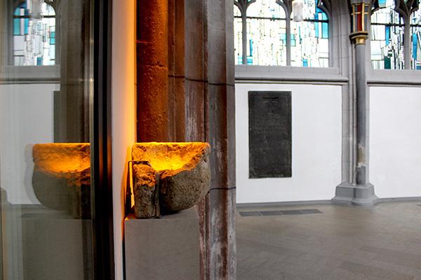 """Etwa 1.000 Jahre jünger als die antiken Überbleibsel der Römer und Jahrhunderte älter als die heutige AntoniterCityKirche ist das Weihwasserbecken des Sackbrüderordens von 1260. Als Zeichen für die ungeteilte Kirche hat es einen unübersehbaren """"goldenen P"""