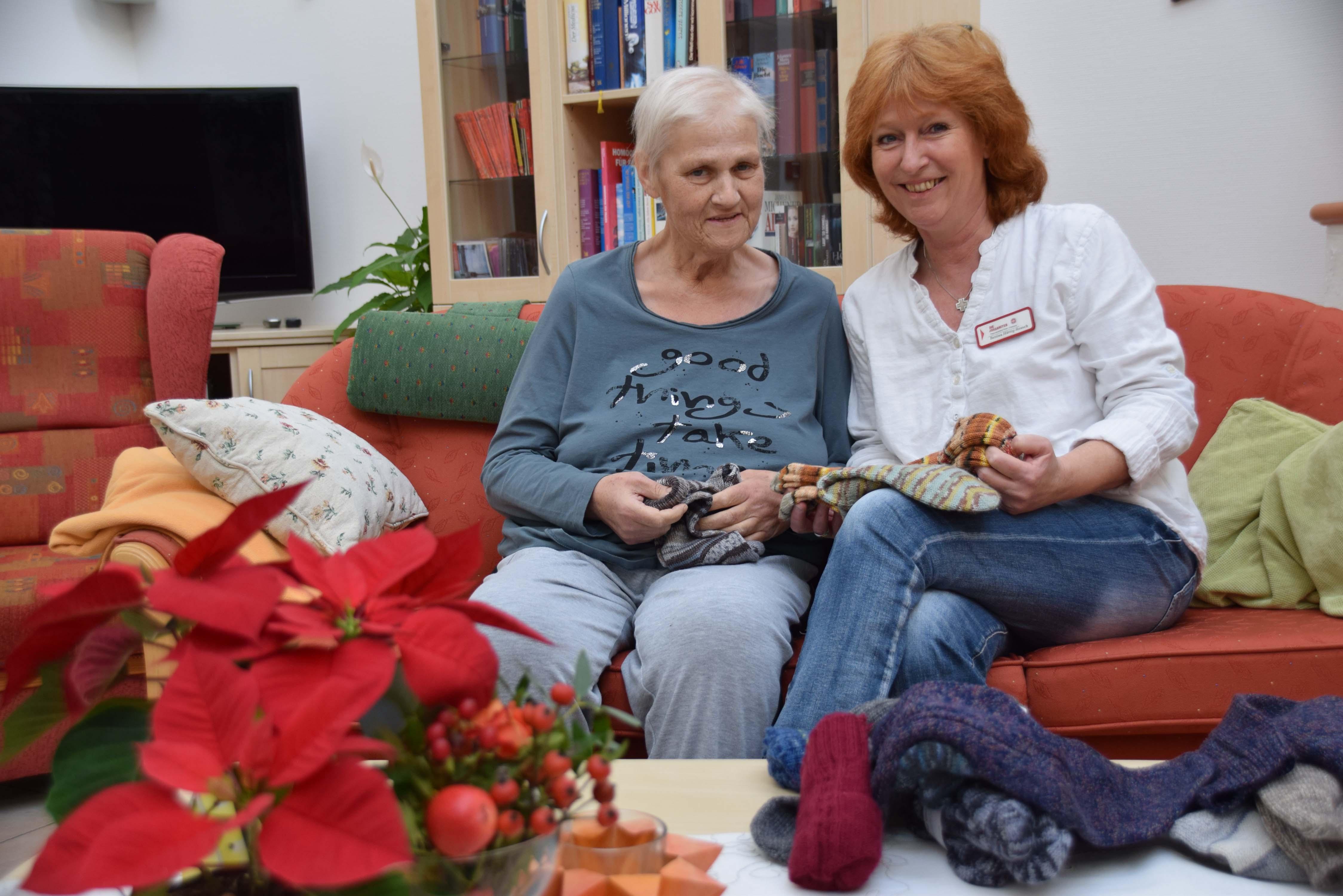 Bequeme  Kleidung will Krankenschwester Bettina Hüttig-Reusch (rechts) nach ihrem Tod angezogen bekommen. Warme Socken müssen es sein, findet auch Hospizbewohnerin Martina Gemein.