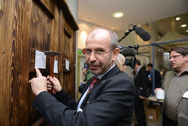 Präses Manfred Rekowski nagelt seine 'Thesen' an die Holztür.