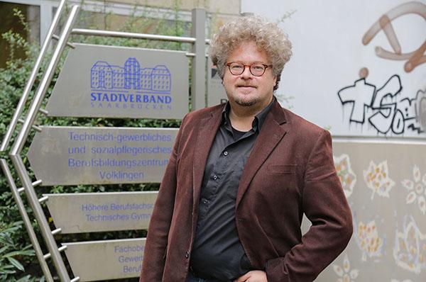 Religionsunterricht funktioniert mit Lachen: Pfarrer Volker Hassenpflug vor dem Berufsbildungszentrum Völklingen.