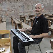 Chefintontateur Gregor Hieke bedient mithilfe der Tatstatur den Orgamaten oben an Orgel aus der Mitte des Raumes  - damit Ton, Klang und Raum perfekt harmonieren.
