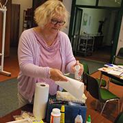 Gemeindepädagogin Katja Spitzer desinfiziert Kleber und Stifte, bevor die nächsten Kinder zur Bastelstation kommen.