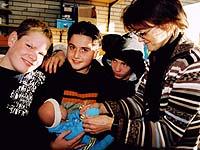 Sigrid Vollstedt von der Bonner Diakonie zeigt den Schülern den richtigen Umgang mit Babys.