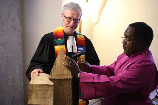Pfarre Stephan Schneider lässt Bischof Benson Bagonza den ersten Nagel in die symbolische Holzkirche schlagen.