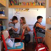 Lehrerin Silke Fislage mit ihren Schülern Miguel und Anthony im Schulwagen.