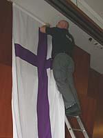 Letzte Aufbauarbeiten: Die Kirchenfahne wird am Kopf des Sitzungssaals der Landessynode aufgehängt.