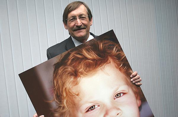 Oberkirchenrat Klaus Eberl mit einem der Porträts der Ausstellung 'Ich bin ich'.