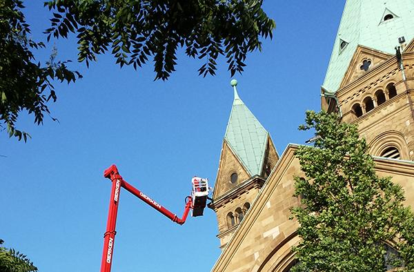 Professionelles Provisorium: Nach dem schweren Unwetter an Pfingstmontag übernimmt ein Dachdecker vorläufige Reparaturarbeiten an der Düsseldorfer Kreuzkirche.