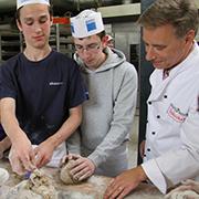 Joshua (v.l.) und David mit Bäckermeister Terbuyken beim Backtermin.