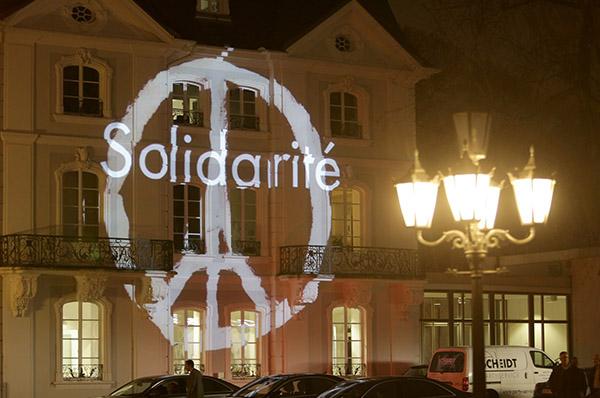 Solidarité und der Eiffelturm als Friedenssymbol auf einem Gebäude der saarländischen Staatskanzlei neben der Kirche am Ludwigsplatz.