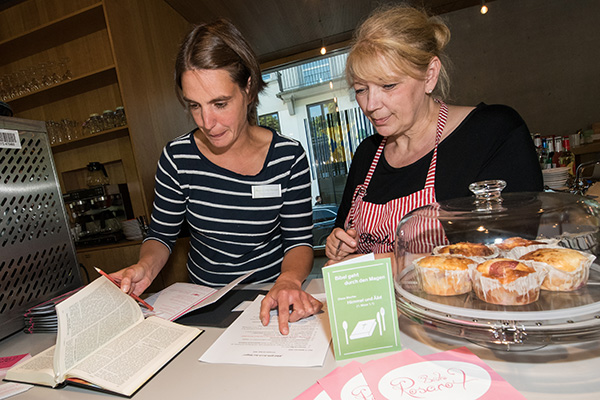Die Bibel konsultieren: Pfarrerin Ulrike Verwold und Küchenchefin Kornelia Kraemer (l.) bringen jede Woche ein neues biblisch inspiriertes Gericht auf die Speisekarte im Bonner Kirchenpavillon.