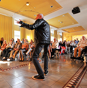 Herr Boskamp tanzt, während Frau Höpker zum Gesang bittet.