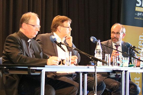 Podiumsdiskussion in Aula der Saar-Uni mit dem Trierer Bischof Stephan Ackermann (li) und dem rheinischen Präses Manfred Rekowski (re). Moderiert hat Christian Otterbach vom Saarländischen Rundfunk (mitte).
