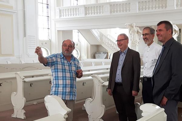 Peter Böttcher (v.l.), Christian Weyer, Thomas Bergholz und Martin Wendt erklären die Renovierungen im Innenraum der Saarbrücker Ludwigskirche.