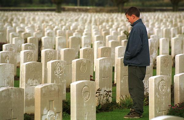 Ein Junge steht zwischen Grabsteinen für gefallene Soldaten des Ersten Weltkrieges auf 'Tyne Cot' bei Passendale, dem größten der 160 britischen Soldatenfriedhöfe im belgischen Flandern.