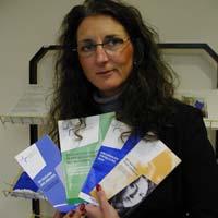 Stolz präsentiert Eva Schüler aus der Pressestelle die Broschüren im neuen Design