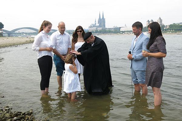 Pfarrer Mathias Bonhoeffer aus Köln tauft bei Stromkilometer 689,5 im Rhein.
