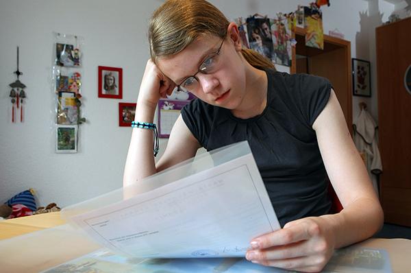 Sorgenvoller Blick ins Schulzeugnis: Vor den Sommerferien gibt es Zeugnisse. Foto: epd-bild/Stefan Arend