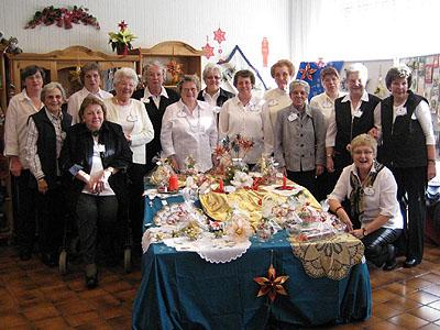 All together: die Handarbeitsgruppe der Kirchengemeinde Moers-Scherpenberg im kleinen Gemeindesaal mit Verakufsschränken und -tisch.