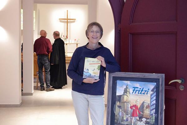 Hanna Schott mit Buch und Filmplakat in ihrer Kirchengemeinde. Der Animationsfilm 'Fritzi - eine Wendewundergeschichte' startet am 9. Oktober in den deutschen Kinos.