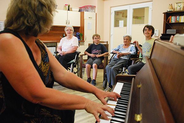 Seniorinnen und Kinder singen zusammen, die Bergische Diakonie bringt sie zusammen.
