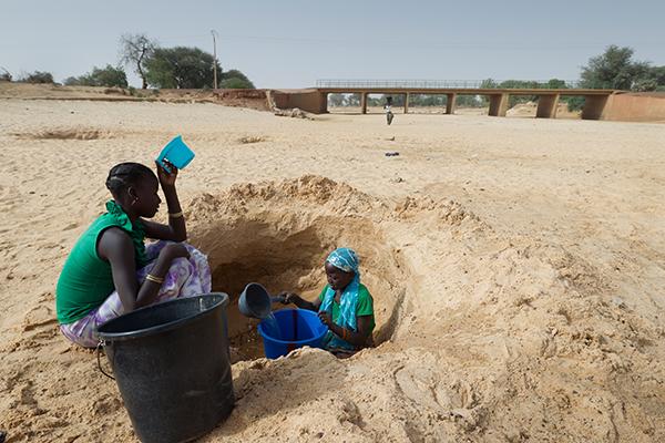 Im fast ausgetrockneten Flussbett des Kakassi River in Niger versuchen die Menschen trinkbares Wasser, das sich in den gegrabenen Löchern sammelt, zu schöpfen.