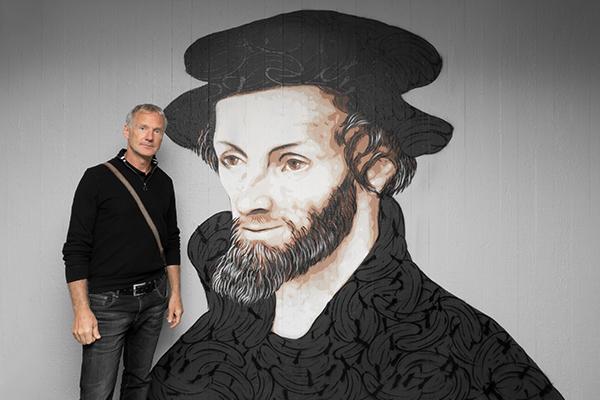 Der Künstler Thomas Baumgärtel, auch bekannt als Bananensprayer,  vor seinem Melanchthon-Porträt. im Landeskirchenamt. Sein Markenzeichen, die Banane findet sich auch vielfach in dem Kunstwerk wieder.