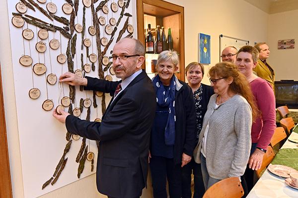 Präses Manfred Rekowski darf sich als Spender auf einem Holzplättchen verewigen, denn die Hälfte der Kollekte aus dem Eröffnungsgottesdienst der Synode geht an das Projekt.