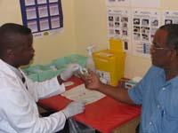 Pastor Imms Mberira (links) bereitet im kirchlichen Gesundheitszentrum von Otjiwarongo in Namibia einen Aidstest vor.
