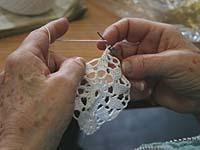 Mehrere Frauen aus der Handarbeitsgruppe häkeln und sticken mit großer Erfahrung.