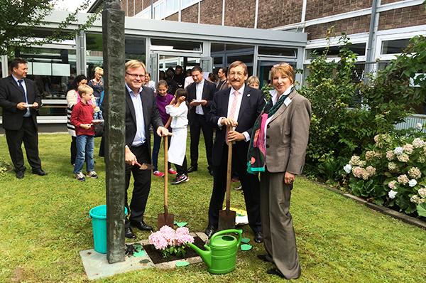 Pflanzen eine Hortensie zur Eröffnung der neuen Gesamtschule: Bürgermeister Stefan Caplan (vorn, v.l.), Oberkirchenrat Klaus Eberl und Rektorin Angelika Büscher.