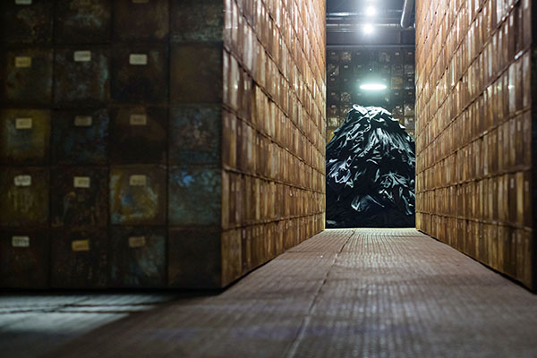 Für die Installation 'Die Zwangsarbeiter' bilden schwarze Hosen und Jacken inmitten von metallenen Archivkästen in der Sinteranlage einen Kleiderberg. Foto: epd-bild / Oliver Dietze